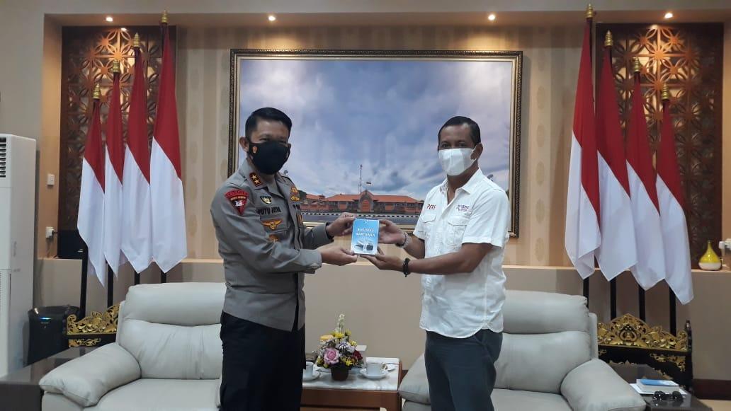 Ketua SMSI Bali, Emanuel Dewata Oja menyerahkan buku berjudul 'Buku Saku Wartawan' kepada Kapolda Bali Irjen Pol Putu Jayan Danu Putra