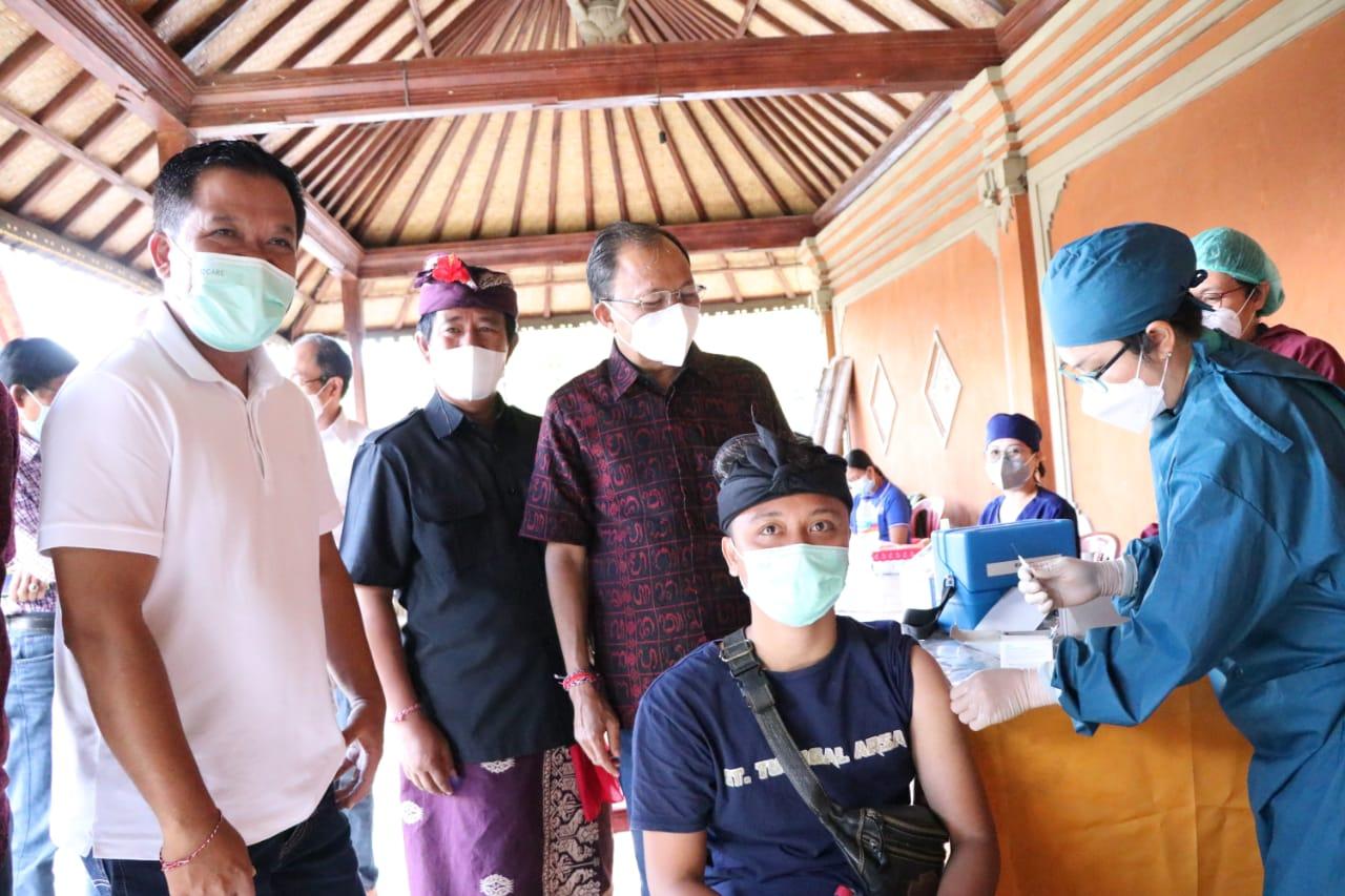 Gubernur Bali, Wayan Koster (Lima dari kiri) sempatkan diri berkomunikasi dengan beberapa anggota masyarakat yang tengah menerima suntikan vaksin covid-19. (FOTO: Ist)