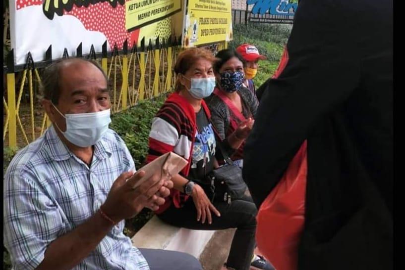 Salah seorang warga menerima nasi bungkus yang dibagikan mahasiswa BEM FH Unud. (FOTO/Ist)