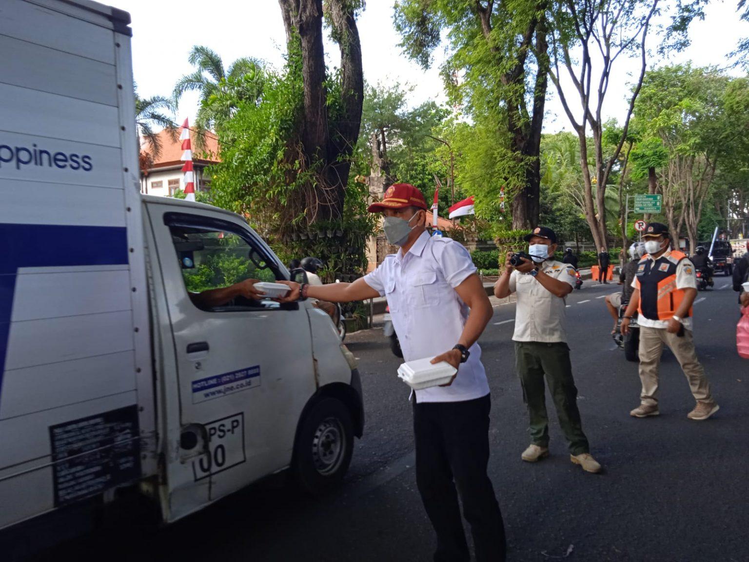 Kasatpol PP Provinsi Bali, I Dewa Nyoman Rai Dharmadi, SH.,MSI. membagikan bingkisan Berbagi Kasih kepada warga.